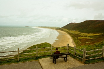 A man reads a book on a bench overlooking Rhossili Bay. Image: Catrin Austin (Flickr)