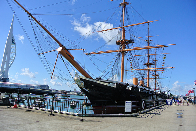 HMS Warrior sits in Portsmouth Historic Dockyard, with the famous Spinnaker tower in the background. Image: Paul Lewin, Flickr.